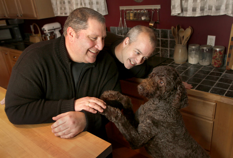 David Jacobs, left, and Paul Jacobs play with their dog Godiva in their home in South Portland on Friday. The couple of 22 years recently got engaged and plan to get married in July.