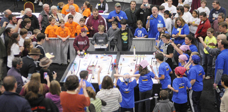 Team members and spectators gather a round a table as a pair of teams compete at the 13th annual Maine First LEGO League Championship on Saturday, at the Augusta Civic Center.