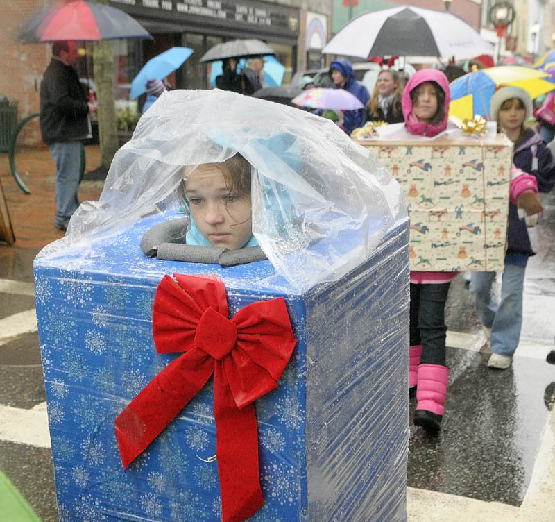"Thekla Jubinville wears a rain poncho over her wrapped present costume, as she marches down Water Street in the ""Who's Your Favorite Who"" parade on Saturday, in downtown Gardiner. Despite the rain the parade went on and Santa and Mrs. Claus arrived in a horse drawn wagon."