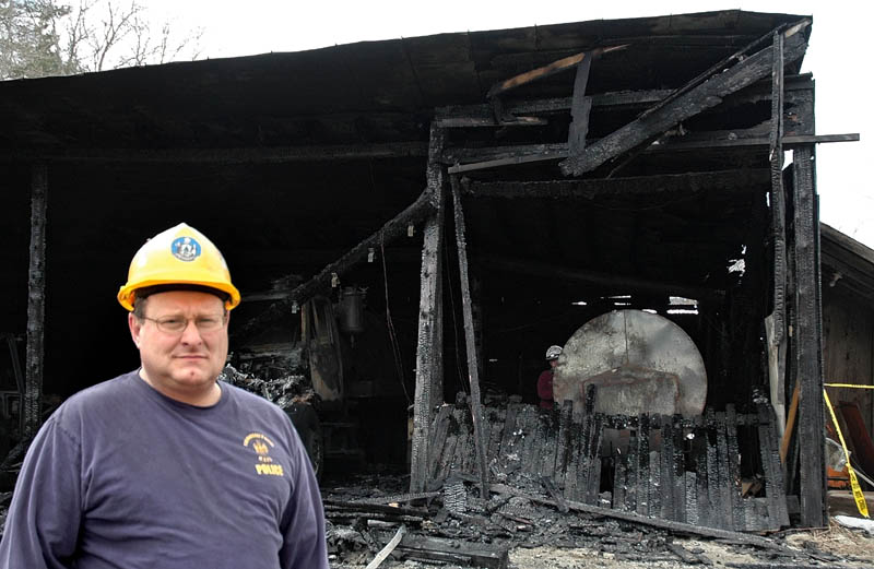 Sgt. Joel Davis of the State Fire Marshal's Office helped investigate the arson in Bingham over the weekend. Behind him is the public works garage, damaged in one of the arsons.