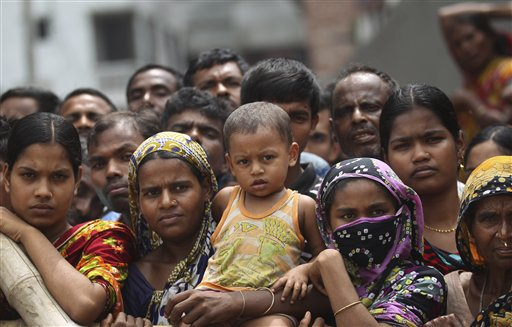 Curious onlookers and relatives of missing victims watch from behind a fence as workers start removing pieces of the garment factory building that collapsed in Savar, Bangladesh.