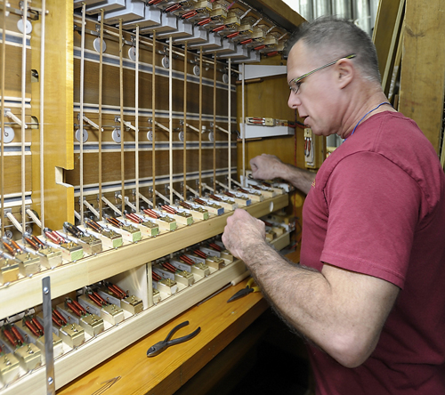 Technician David DeBlois adjusts and connects internal barrow pull-down actions on a manual chest for the solo division of the organ as he and other technicians work on refurbishing the Kotzschmar Organ from Merrill Auditorium in Portland, Maine at Foley-Baker, Inc. in Toland, Connecticut.