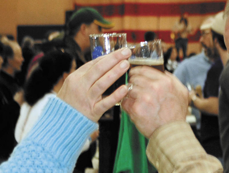 John Chapin, left, and Diana Chapin, of Montville, clink sample glasses on Saturday during the Central Maine Brew Fest at the Augusta armory.
