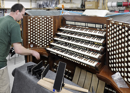 Adam Lagocki works on The Console of the organ as he and other technicians work on refurbishing the Kotzschmar Organ from Merrill Auditorium in Portland, Maine at Foley-Baker, Inc. in Toland, Connecticut.