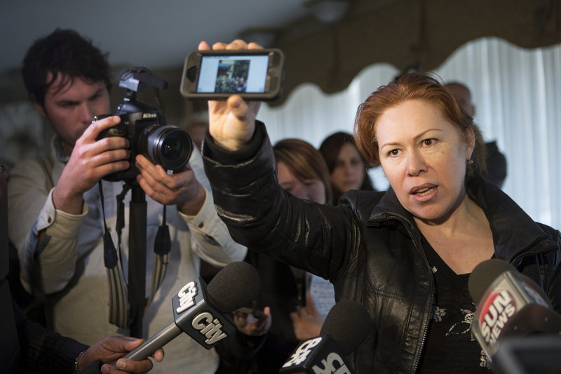 Maret Tsarnaev, an aunt of the two suspects in the Boston Marathon bombing, holds a reporter's smartphone, which displays a scene from the bomb site, as she speaks to journalists Friday at her apartment building in Toronto.