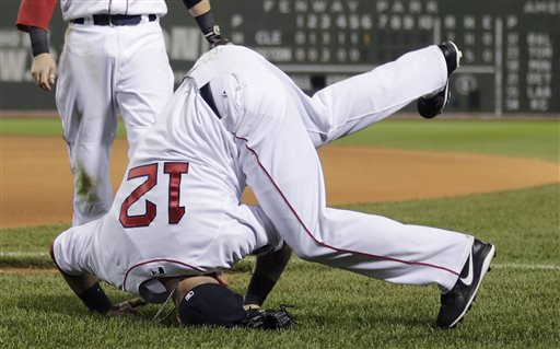 Boston Red Sox first baseman Mike Napoli (12) lands on his head while missing the catch on a foul by Cleveland Indians' Yan Gomes in the seventh inning of a baseball game at Fenway Park in Boston, Thursday, May 23, 2013. (AP Photo/Charles Krupa)
