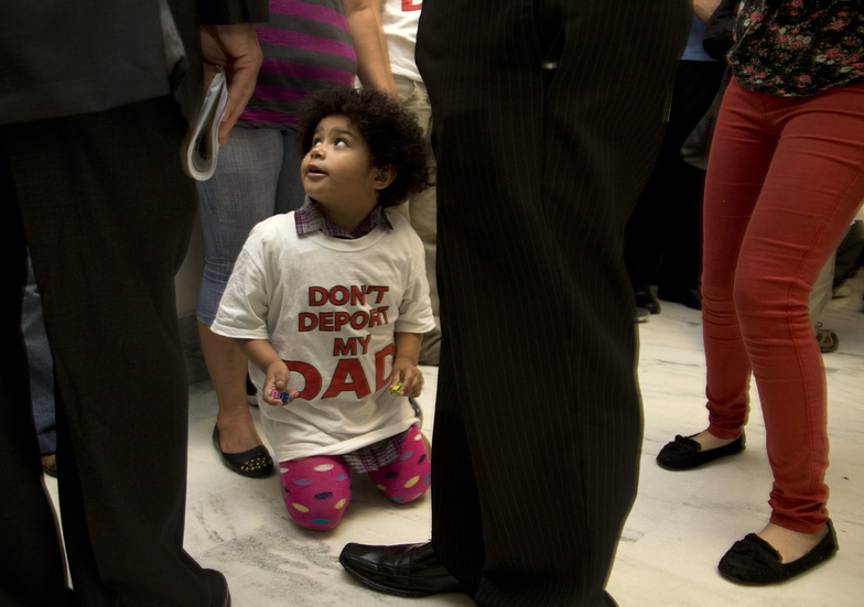 "Jackelin Alfaro, 4, in a T-shirt that reads ""Don't Deport my Dad,"" sits in the hall with family members outside the House Judiciary Committee hearing on Capitol Hill in Washington on Tuesday."