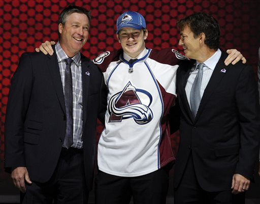 Nathan MacKinnon stands with officials from the Colorado Avalanche sweater after being chosen No. 1 overall in the first round of the NHL draft on Sunday in Newark, N.J.
