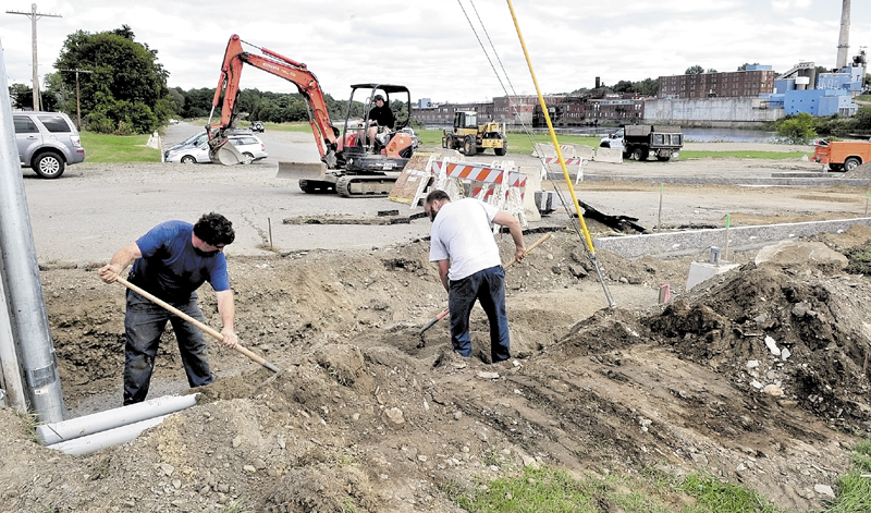 Workers bury electrical conduits beside new granite-lined walkways in the landscaping project at Head of Falls in Waterville in 2010.