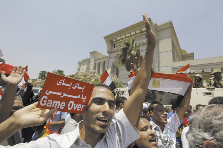 "Egyptians celebrate after Egypt's chief justice Adly Mansour is sworn in as the nation's interim president Thursday. The Arabic on the sign reads, ""bye bye Morsi."""