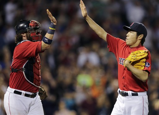 Boston Red Sox relief pitcher Koji Uehara, right, is congratulated by catcher Jarrod Saltalamacchia after striking out Toronto Blue Jays' J.P. Arencibia to end the top of the eighth inning of a baseball game at Fenway Park, Friday in Boston.