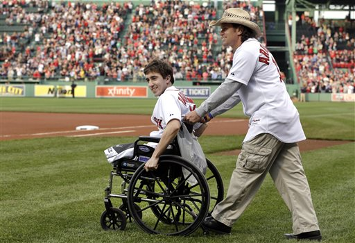 Boston Marathon bombing survivor Jeff Bauman is wheeled onto the field by Carlos Arredondo, the man who helped save his life, to throw out the ceremonial first pitch at Fenway Park on May 28, 2013.