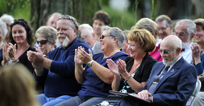 Cathy Taylor, widow of Bill Taylor, second from left, shares a laugh with 450 other friends of her late husband as they remember and celebrate his life at Castonguay Square in downtown Waterville today.