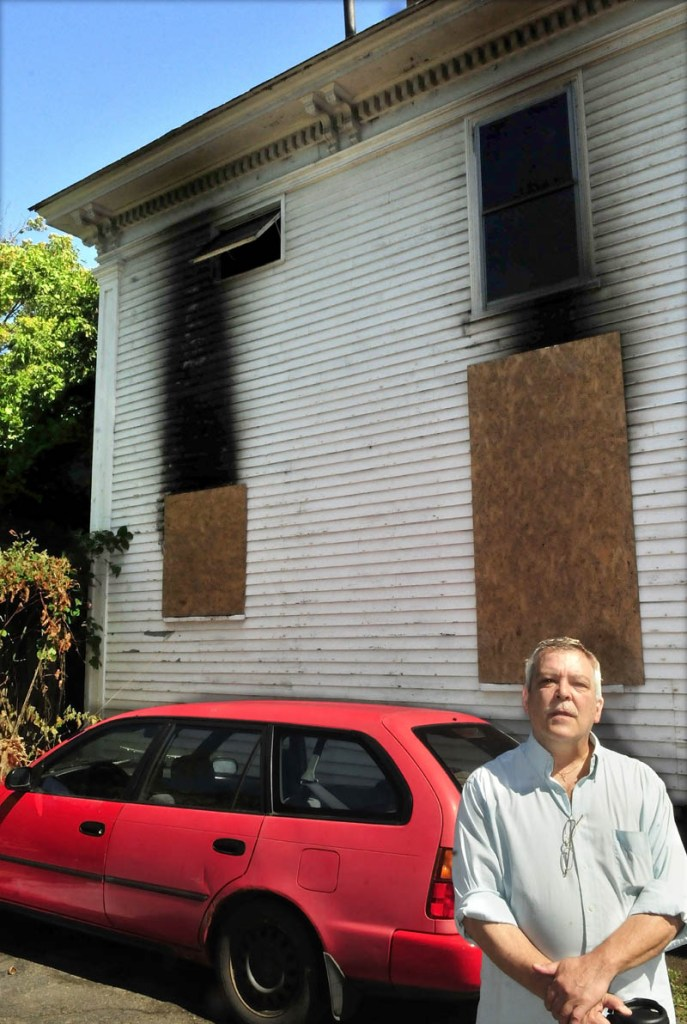 Wes Berry's home was only feet from the house that was destroyed by fire on August 25 on Elm Court in Waterville. Exploding window glass covered his driveway and vehicle. Berry and other neighbors want the building razed.