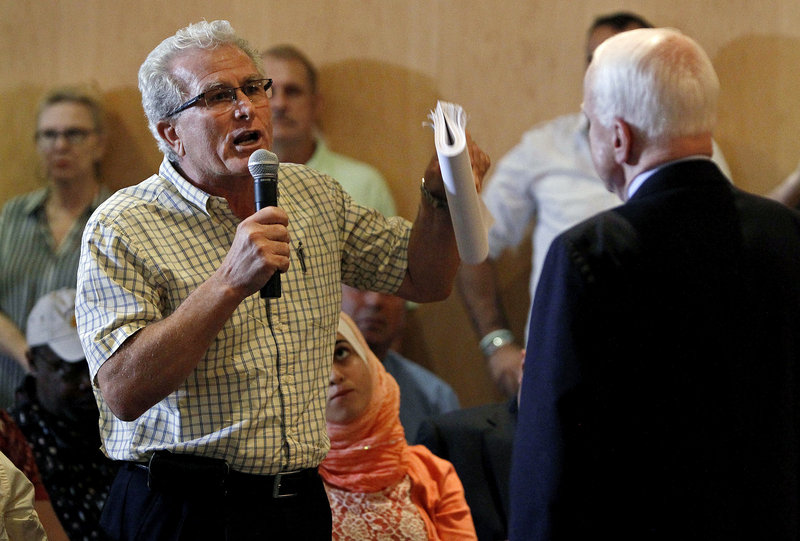 Sen. John McCain, right, who generally supports President Obama's stance, hears a dissenting point of view from constituent Albert Moussa earlier this week during a town hall meeting in Phoenix that was supposed to concern various issues but quickly focused on possible military action against Syria.