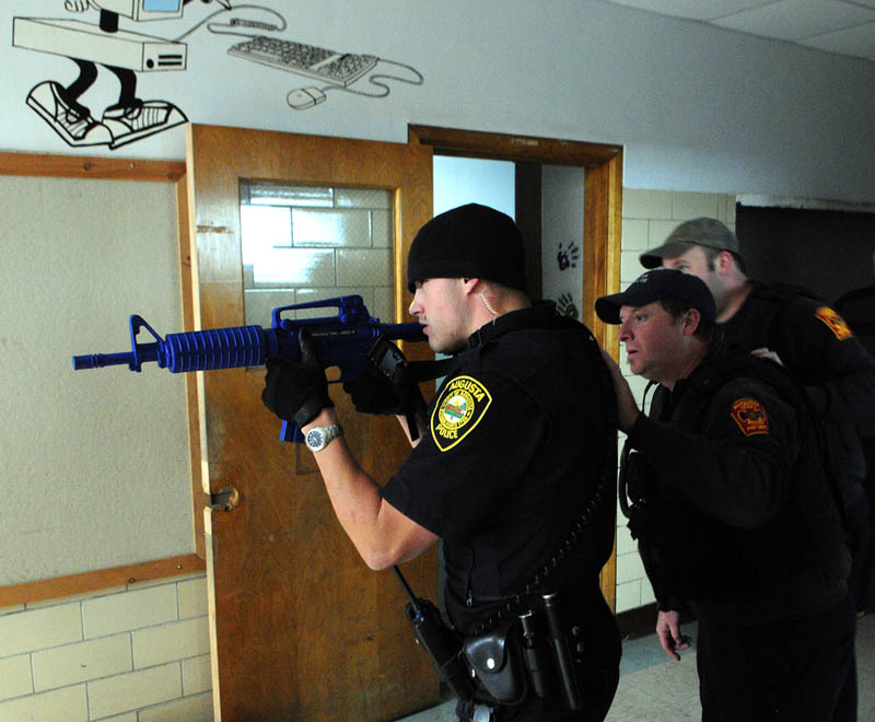 Augusta Police officer Nico Hample, left, leads Augusta firefighter/paramedics John Robertson and Jason Decker as they move down a hallway during a training exercise Friday at the former Hodgkins middle school in Augusta.