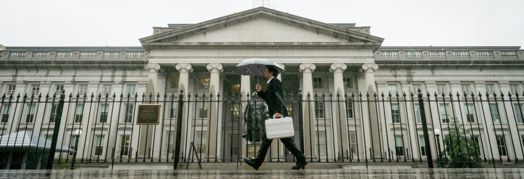 A pedestrian walks past the U.S. Treasury Building in Washington on Thursday, as the federal government shutdown continued.