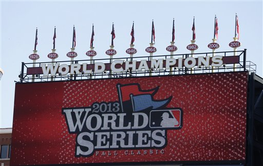Flags fly over a scoreboard during baseball practice, Friday, Oct. 25, 2013, in St. Louis. The St. Louis Cardinals and Boston Red Sox are set to play Game 3 of the World Series on Saturday in St. Louis.
