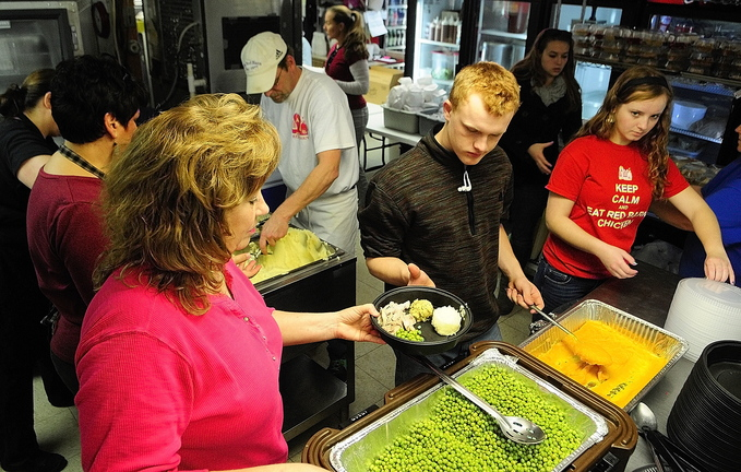 Load her up: Volunteers load up turkey dinners on plates for the community Thanksgiving dinner today at The Red Barn in Augusta. Plates had turkey, stuffing, potatoes, peas and squash.