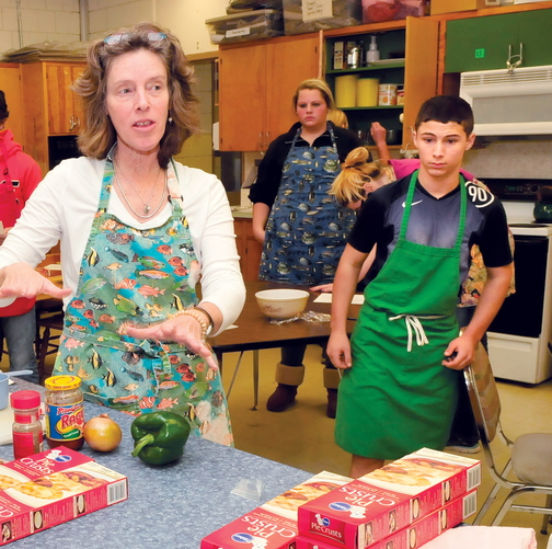 THE BASICS: Skowhegan Area High School teacher Beth Scherpf speaks with students in the Basic Foods class last month. At right, student Jeremy Silva prepares to make pizza pockets.