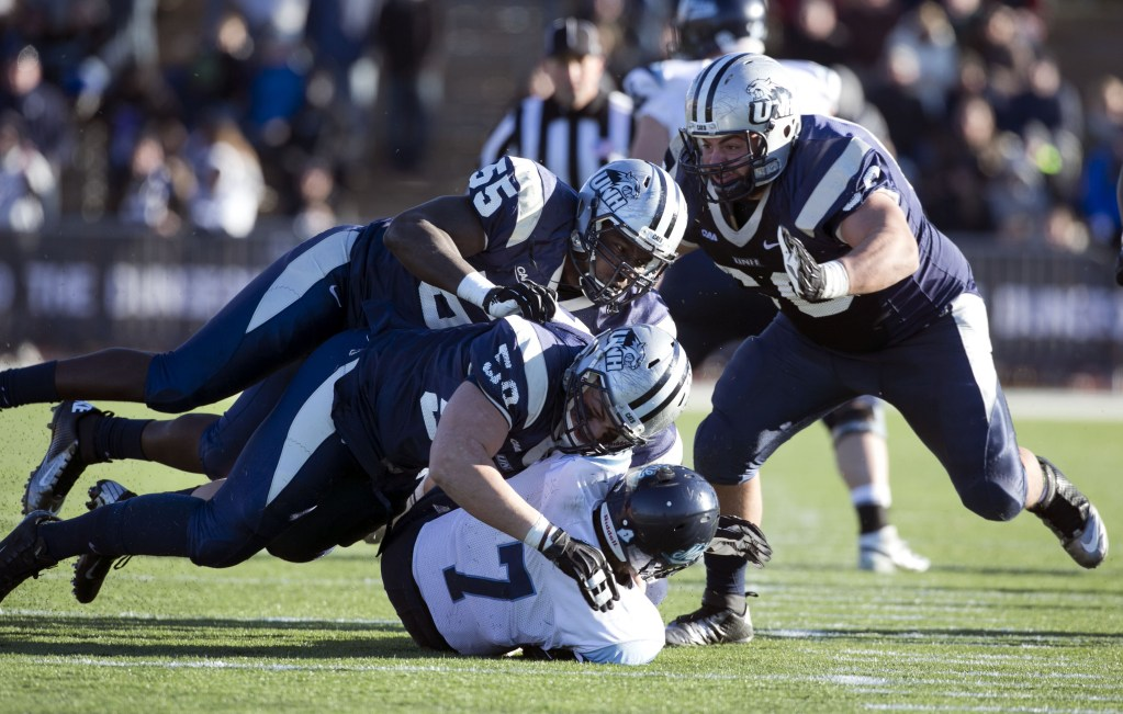 Maine quarterback Marcus Wasilewski (7) gets sacked by New Hampshire's Sean McCann (58), Jay Colbert (55) and Matt Kaplan (60) in the second half of an NCAA.