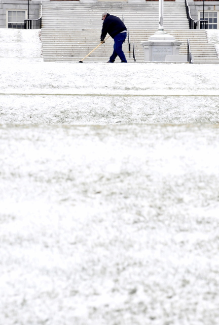 Staff photo by David Leaming HERE WE GO AGAIN: Colby College employee Earl Michaud shovels snow from the sidewalk in front of Miller Library in Waterville on Tuesday. Michaud rolled his eyes at the thought of the long winter and work ahead.
