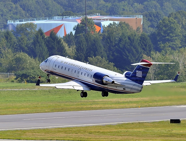 US Airways Express Flight 3722 takes off for Philadelphia from the Portland International Jetport and flies over the oil tanks in South Portland. US Airways, the largest carrier in Portland, will be merging with American Airlines.