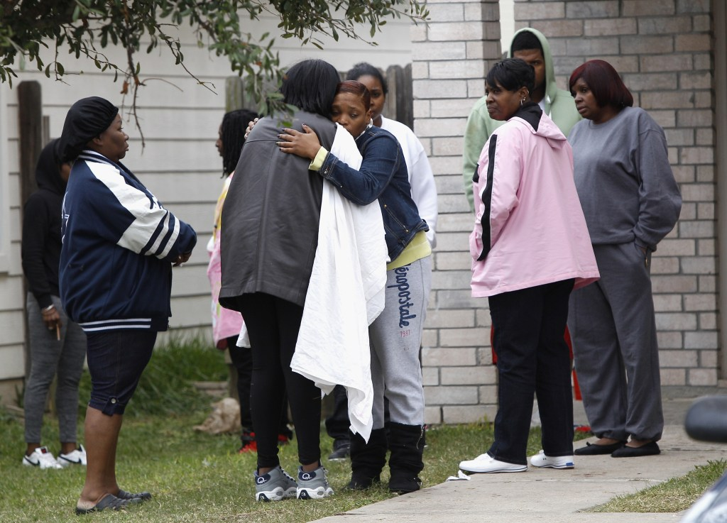 Family and friends console each other outside 7318 Enchanted Creek in Cypress, Texas, on Sunday, after two people were killed and at least 22 others were injured Saturday night when gunfire rang out at a large house party in a Houston suburb, sending partygoers fleeing in panic, authorities said. Authorities say they're seeking two gunmen.