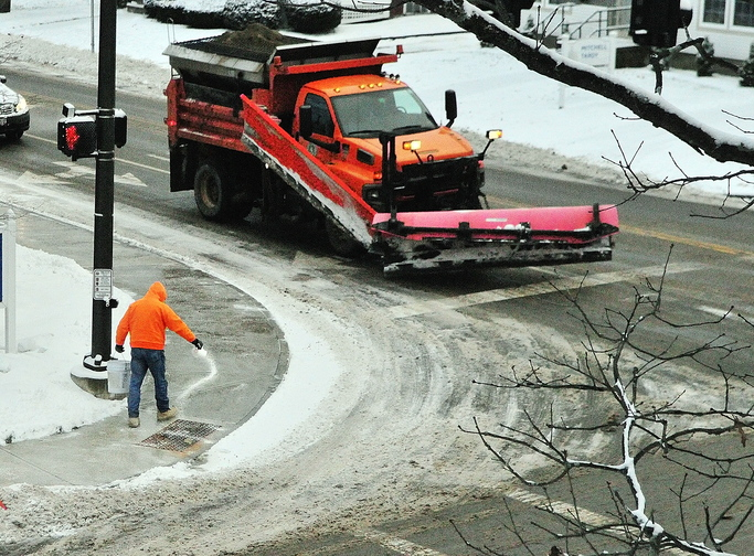 A person scatters salt on the sidewalk next to a City of Augusta snowplow at the corner of Capitol and Sewall Streets on Tuesday in Augusta. People were out across the region with all types of snow removal gear.