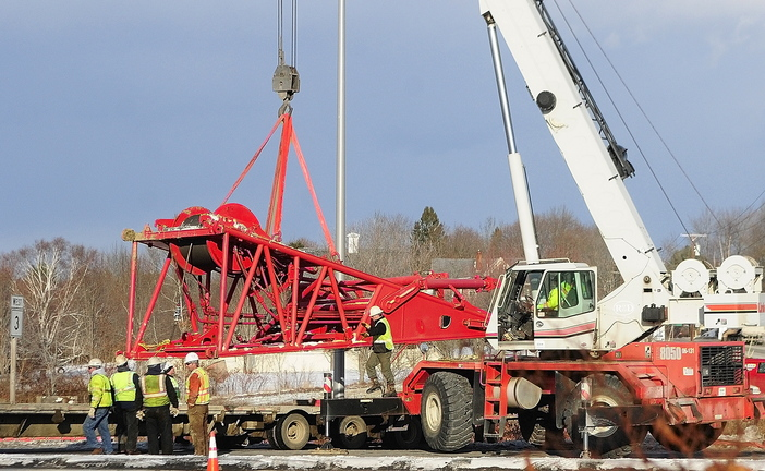 Needs a Lift: Workers use a tow truck to retrieve a crane section Wednesday at the intersection of U.S. Route 201 and Route 3 in Augusta. It had fallen off a tractor-trailer earlier in the day while the tractor-trailer was turning off U.S. Route 201 toward the Cushnoc Crossing bridge on Route 3.