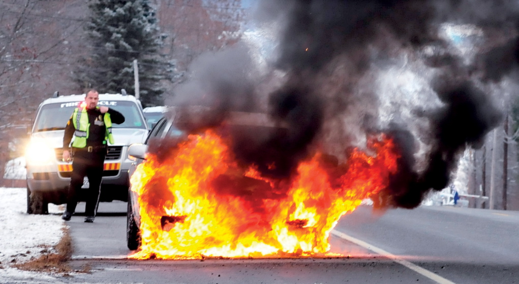 """Fairfield Police Sgt. Paul St. Amand monitors a car that burst into flames on Norridgewock Road on Tuesday. Driver Margaret Genest said at the scene that the car was not accelerating normally and she pulled off the side of the road. A moment later she said she saw smoke followed by fire coming from under hood. """"That's when I decided to get out,"""" said Genest, of Fairfield. The car was extinguished and traffic resumed. There were no injuries, according to St. Amand."""