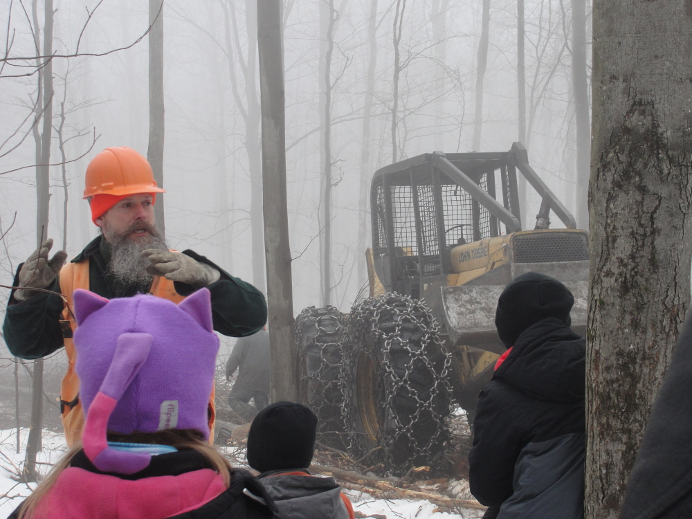 Morton Moesswilde, a district forester with the Maine Forest Service, instructs fourth-grade students from Regional School Unit 4 — Litchfield, Wales and Sabattus — on forestry and logging practices recently in Litchfield. More than 100 students attended the field trip, on Oak Hill Road, where they saw logging and sawmill equipment in action.