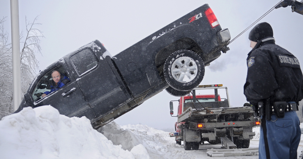 HIGH AND TIGHT: State Trooper Chris Rogers watches as AC Towing pulls a pickup driven by Paul Dubois of Madawaska over a guardrail Thursday at the on-ramp for the northbound lane of Interstate 295 in Gardiner. Dubois' vehicle came to rest several feet down a steep embankment after going over a guardrail in the snow, Rogers said. Two wreckers from AC Towing worked for more than an hour in sub-zero temperatures to pull the pickup back onto the road. Dubois was not injured.