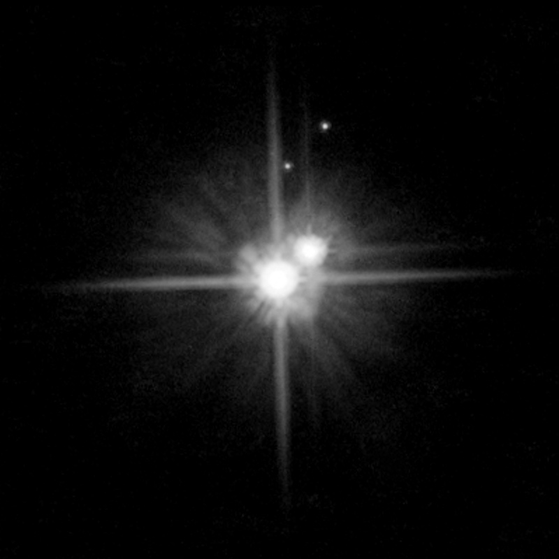 It's cold out there: Pluto and its moons cold in the distant glitter of the sun. Pluto is the large orb at center of image. Charon is the next larger orb to its right.
