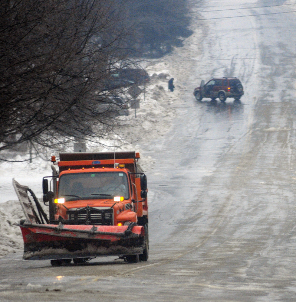 spun around: The driver of a car that spun out in the middle of Winthrop Street waits until a public works truck sands the steep road before trying to drive again on Saturday in Augusta.