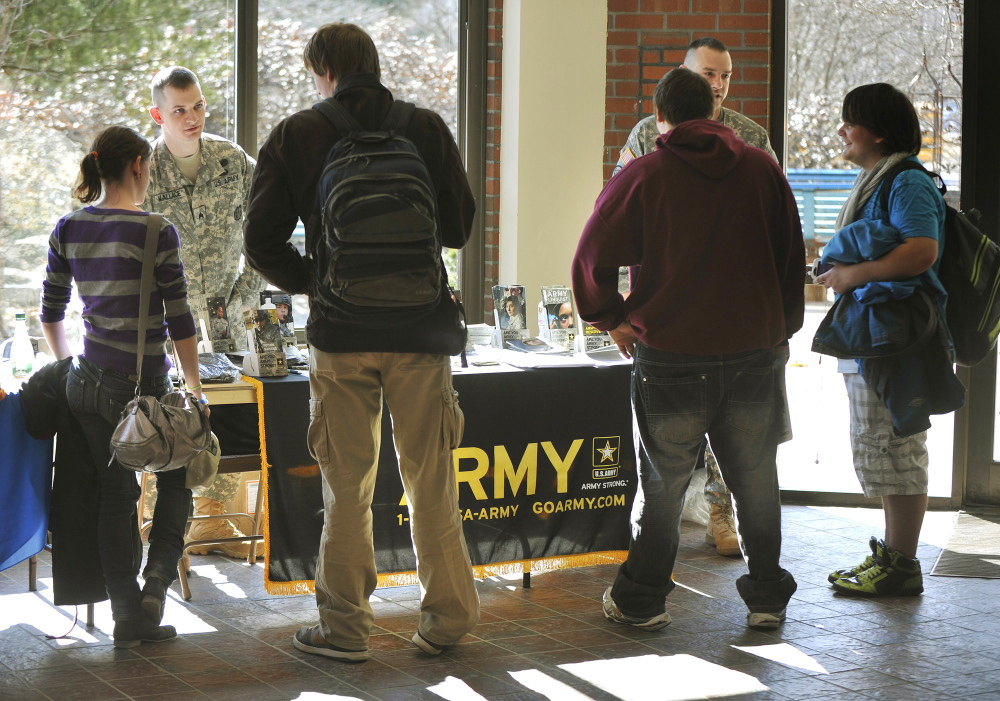 Army recruiters Sgt. Stephen Wallace, left, and Sgt. 1st Class Brandon Didier talk with Portland Arts and Technology High School students during a 2012 job fair. A proposal that would ensure that recruiters are allowed to wear uniforms while visiting schools was approved by a state legislative committee Wednesday.