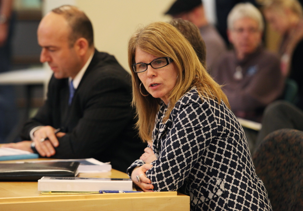 Mary Mayhew, commissioner of the Maine Department of Health and Human Services, shown at a meeting Tuesday in Augusta, says the department has revised its budget shortfall estimate from $108 million to $78 million.