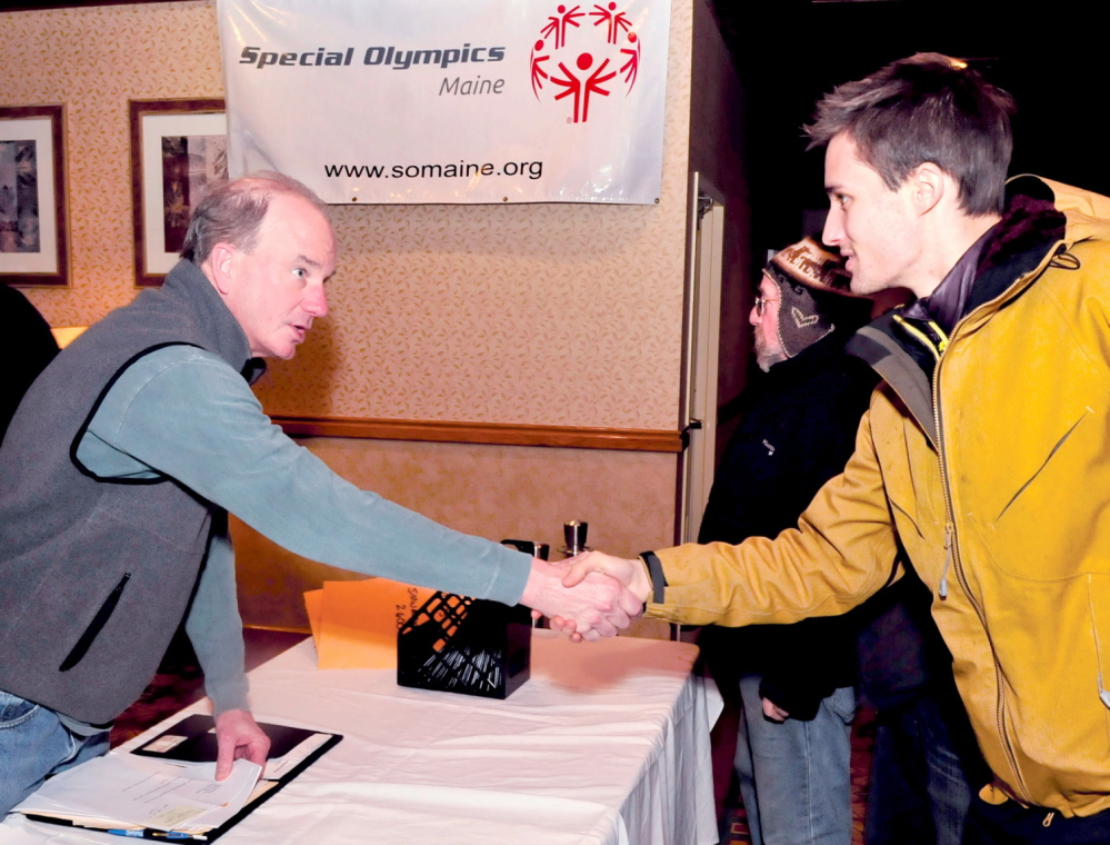 WELCOME: Phil Geelhoed, left, president and CEO of Special Olympics Maine, greets Joshua Nougaret at the volunteer headquarters of the 45th annual Special Olympics Maine Winter Games at Sugarloaf USA on Sunday. Ron Goldstein is in background. Two days of skiing, skating, snowshoe competition and camaraderie begins Monday.