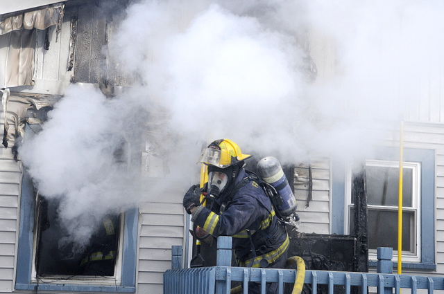 BLAZE: Firefighters enter a burning house Saturday afternoon in West Gardiner. The blaze, reported at 12:45, started in a kitchen at a residence on the Hallowell-Litchfield Road, near Fuller's Market, according to firefighters. One woman who resided in the home was taken to the hospital to be examined for smoke inhalation.