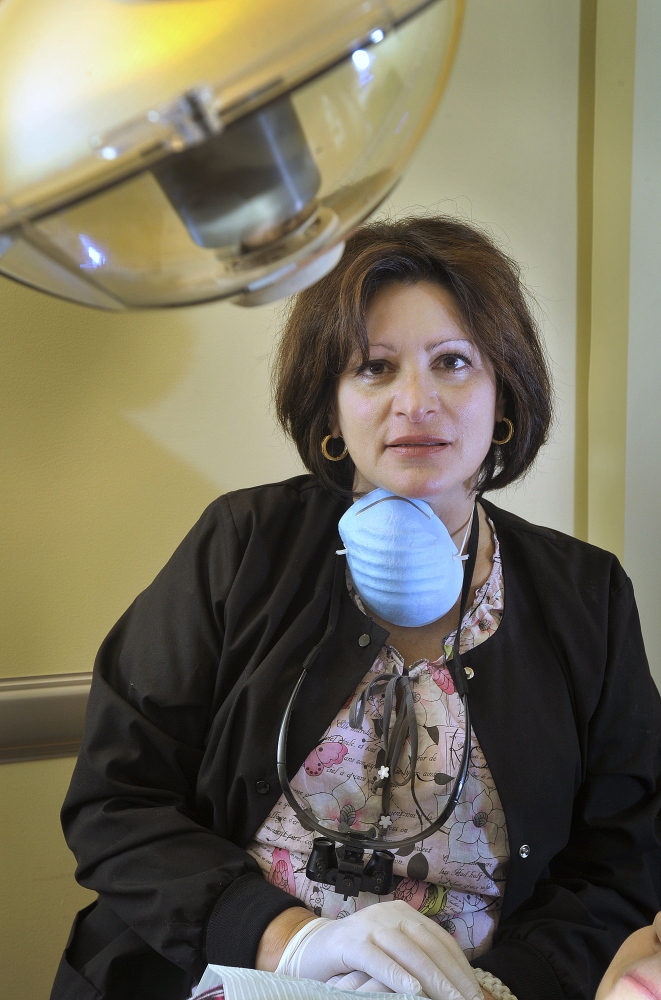 Scarborough dentist Demi Kouzounas and her dental assistant, Sue Cote, work with a patient. Dr. Kouzounas is opposed to efforts in the state Legislature to establish a dental therapy position in the state.