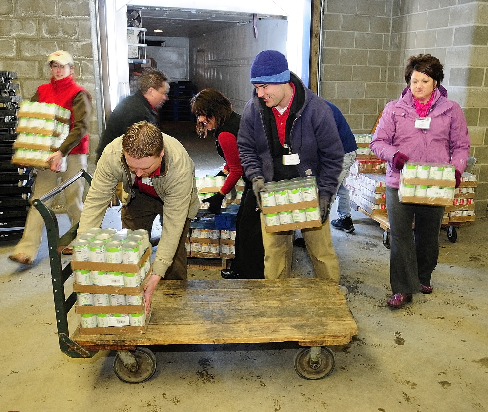 Staff photo by Joe Phelan HELPING HANDS: Hannaford employees from the company's two Augusta stores load donated food onto a cart on Friday February 7, 2014 at the Augusta Food Bank's warehouse.