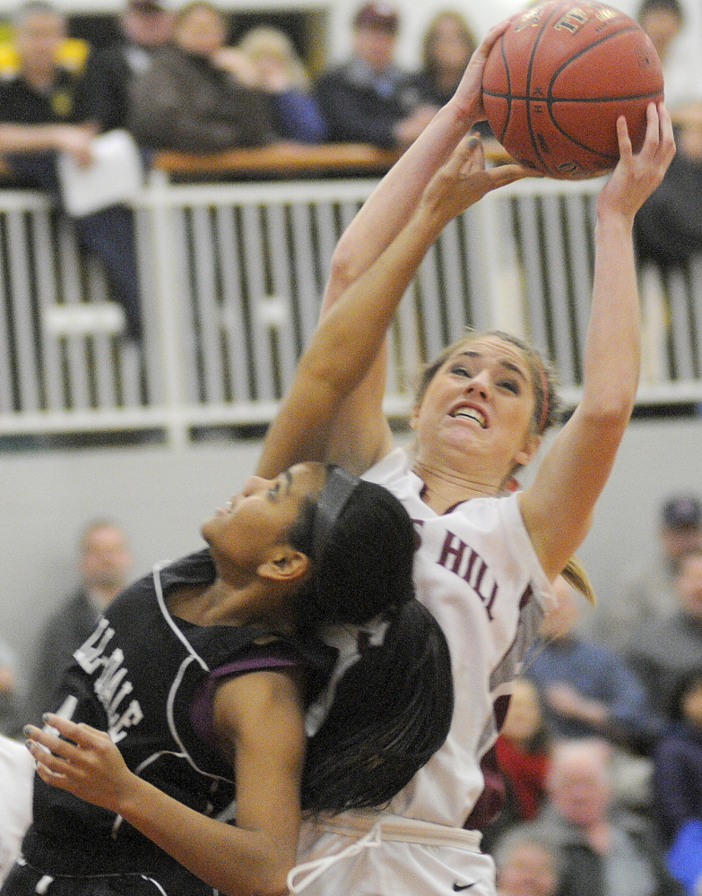 Staff photo by Andy Molloy OVER THE TOP: Kents Hill School's Sara Grenier, right, grabs a rebound away from Hall-Dale High School's Dani Sweet go for a ball during their Western C prelim match Tuesday in Readfield.
