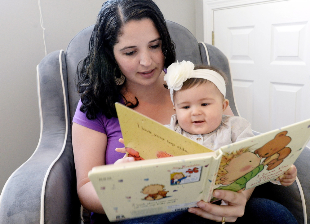 """Hannah Richards of Windham reads to her daughter, Mia, at their home Thursday. """"It's a big help,"""" she said of the $500 grant."""
