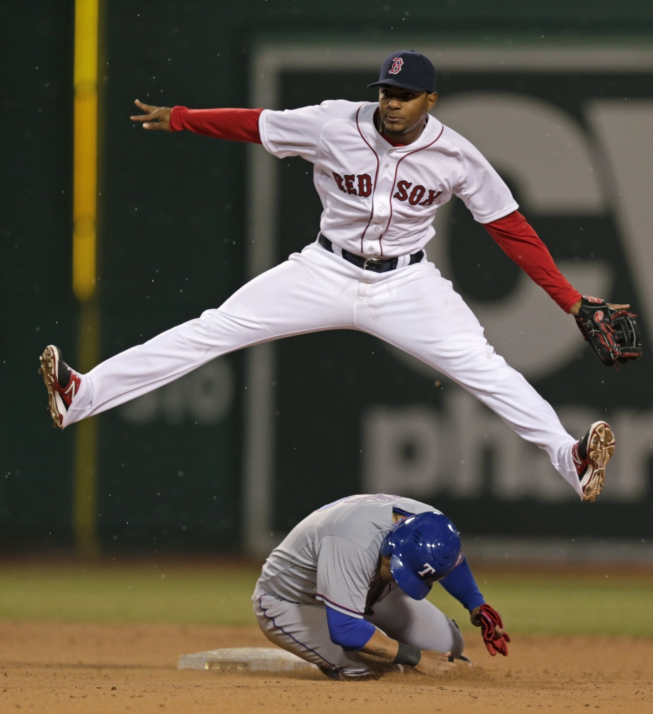 Boston Red Sox shortstop Xander Bogaerts, top, leaps over Texas Rangers left fielder Shin-Soo Choo as he turns a double play during the eighth inning of a MLB American League baseball game at Fenway Park, Monday, April 7, 2014, in Boston.