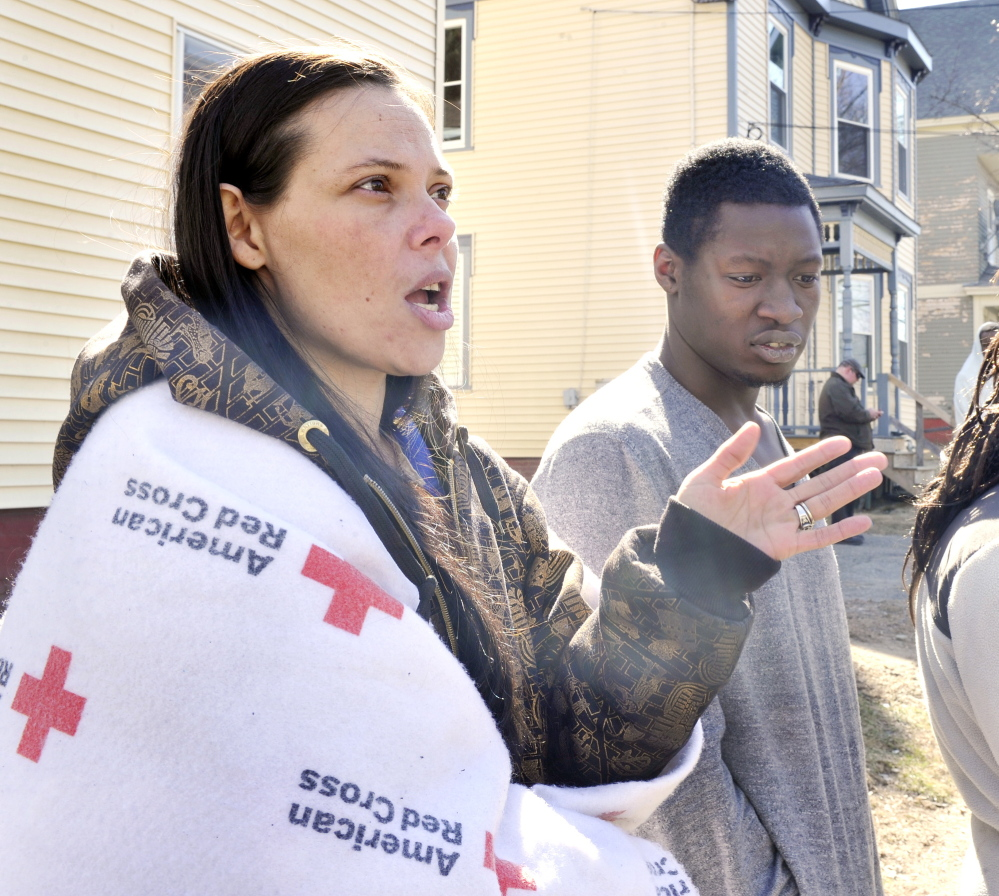 Crystal Thompson describes how she and her boyfriend, Johnny Green (right) were able to escape a building fire on Howe Street in Lewiston that left several dozen people homeless.
