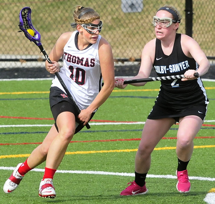 FINDING OPEN SPACE: Thomas College lacrosse player Jillian Lambert runs with ball past Colby-Sawyer player Paige Prokop on Tuesday in Waterville. Thomas won the game 18-2 and will play in the North Atlantic Conference championship game on Saturday.