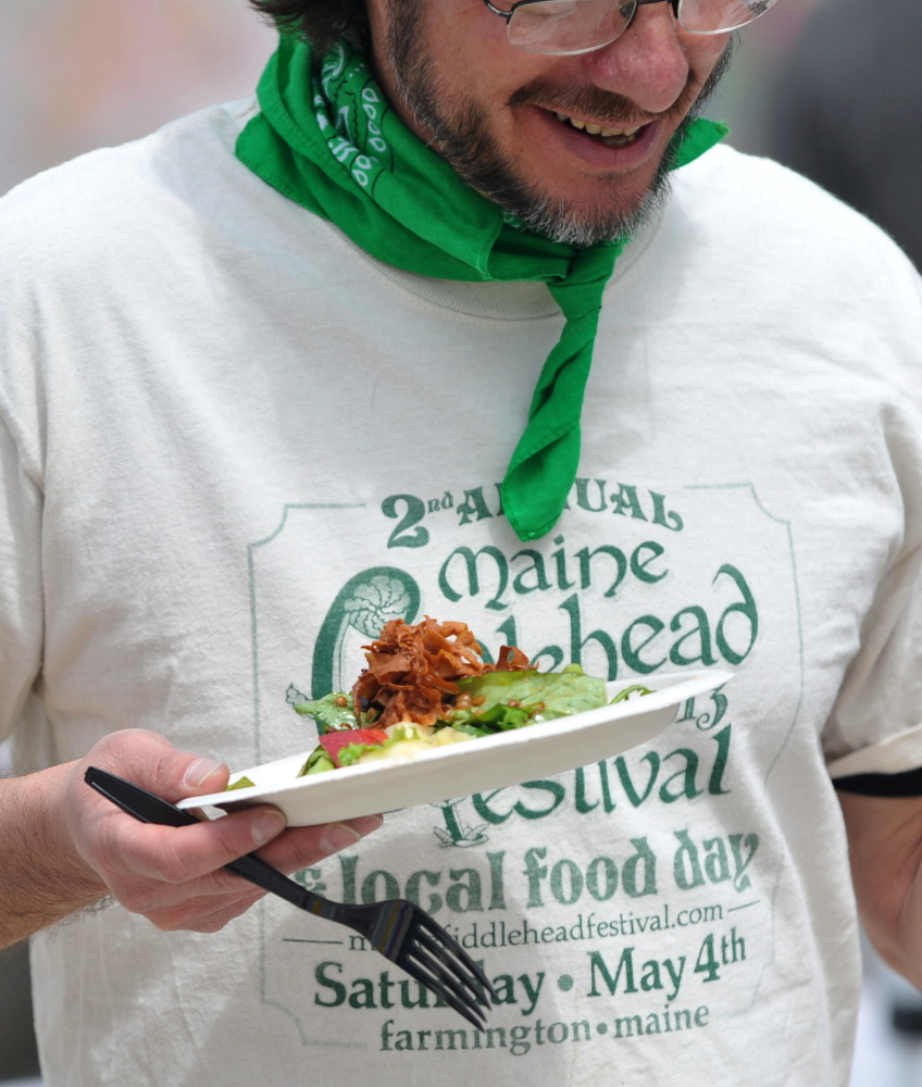 Salad day: Drew Barton tries to find a seat after serving himself a portion of fiddlehead salad during the third annual Fiddlehead Festival in Farmington on Saturday.