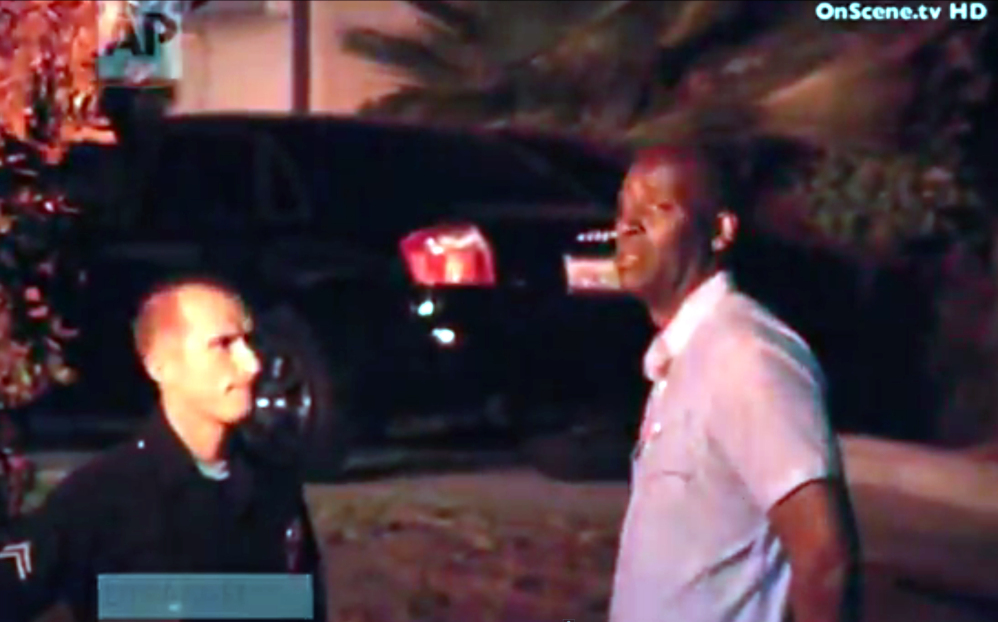 """In this image taken from video from OnScene.tv, actor Michael Jace, right, is detained by police outside his home in Los Angeles on Monday night. Jace, who played a police officer on the hit TV show """"The Shield,"""" was arrested on suspicion of homicide."""