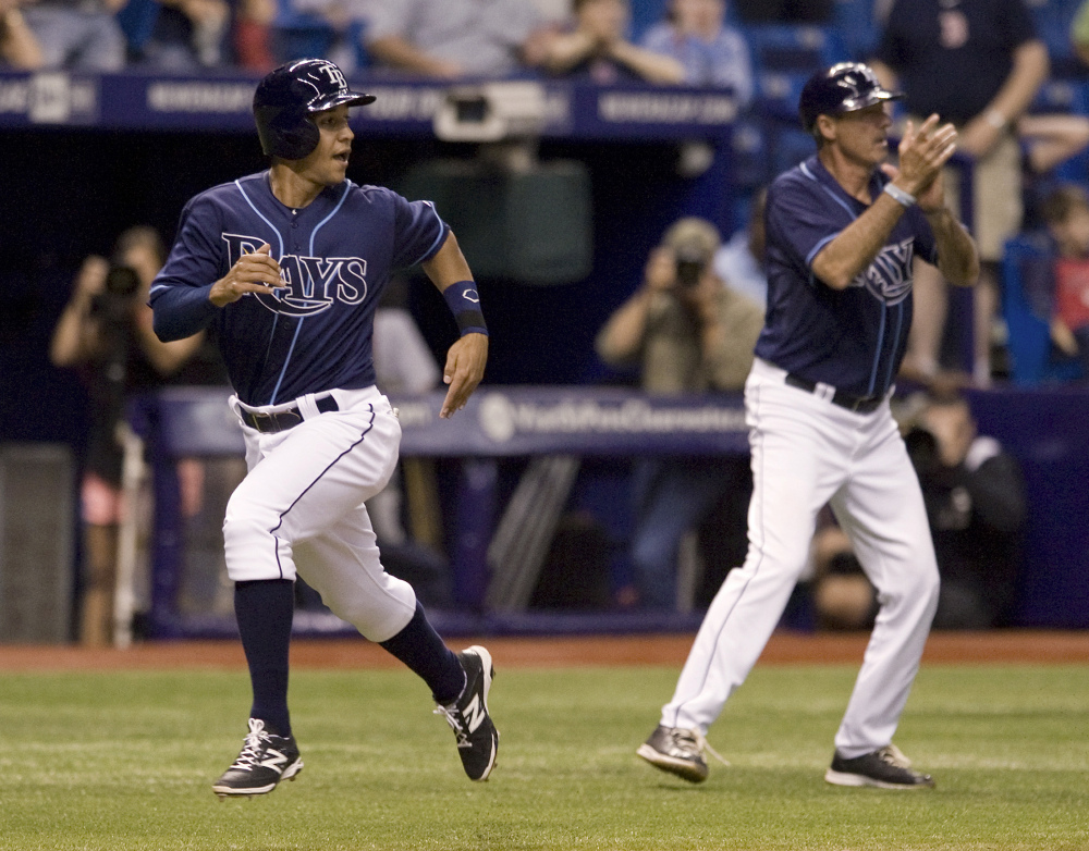 Tampa Bay pinch runner Cole Figueroa races past third-base coach Tom Foley to score the winning run in the 15th inning as the Rays beat the Red Sox, 6-5.