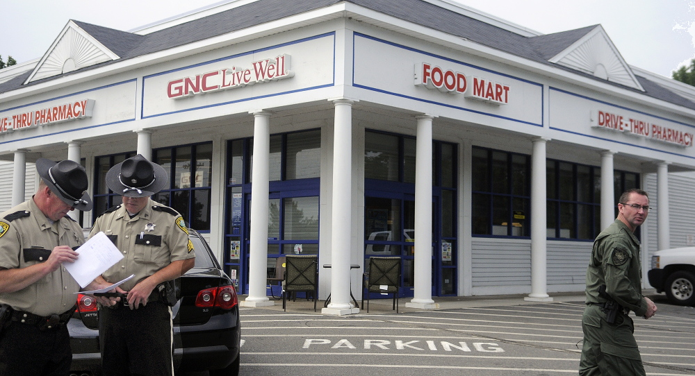 Kennebec County Sheriff's Deputies review photos of a suspect who allegedly robbed the Rite Aid pharmacy in Manchester on Sunday.